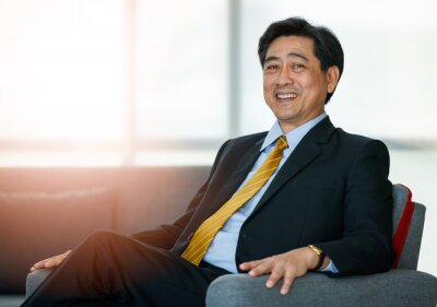 Bild 50s Asian senior executive businessman entrepreneur wearing formal suit with luxury necktie, smart sitting on sofa in indoor office, smiling with confidence, success and gladness with copy space.