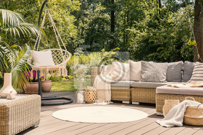 Bild A big terrace with a comfortable leisure sofa with cushions, a table and a string swing in a green garden during sunny vacation.