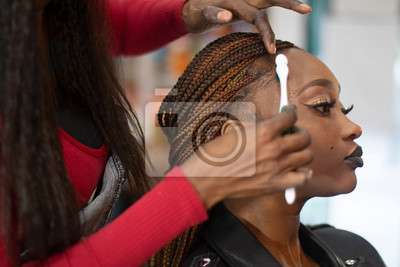 Bild A black hairstylist combing with a toothbrush a beautiful black model.