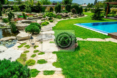Bild A country house with a beautiful backyard behind the house, landscape design