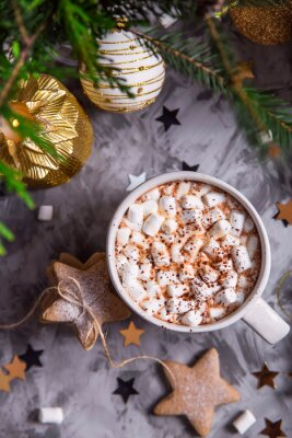 Bild A large cup of cocoa with marshmallow sprinkled with cocoa powder stands on a gray table among Christmas decorations, fir branches, ginger cookies and shiny stars. Top view