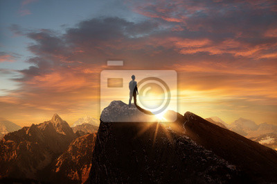 Bild A man standing on top of a mountain as the sun sets. Goals and achievements concept photo composite.