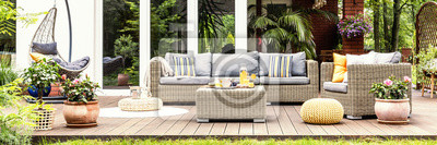 Bild A relaxing spot for a warm, summer day - a stylish, wooden terrace with wicker garden furniture, cushions, plants and flowers