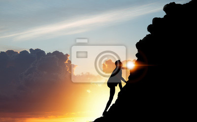 Bild A silhouette of man climbing on mountain top over sunset background, Business, success, leadership, achievement, attempt, patient, endeavor and people concept.