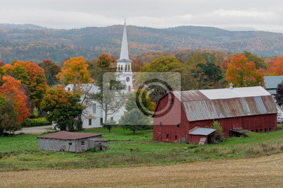 Bild A small church sits on a farm next to a weathered red barn during Autumn