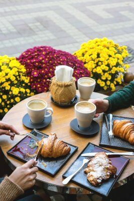 Bild A table in a coffee shop with fresh croissants and cappuccino with female hands in a cozy autumn setting.