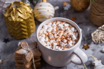Bild A white cup with hot cocoa with marshmallow stands on a gray table among white and gold Christmas ornaments and fir branches
