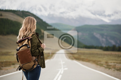 Bild A woman with a backpack and a road stretching into the distance against the backdrop of mountains