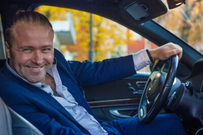Bild a young smiling man businessman in the jacket sitting in the car