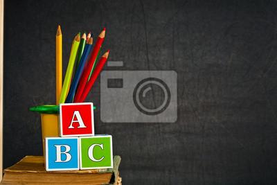 ABC und mehrfarbiger Bleistift auf alten Lehrbuch gegen Tafel
