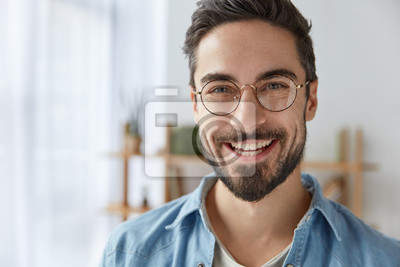 Bild Abschluss herauf Schuss des netten erfüllten attraktiven Mannes mit Stoppel, hat breites Lächeln, trägt runde Schauspiele, freut sich Erfolg bei der Arbeit, Stände gegen gemütlichen Innenraum. Modisch