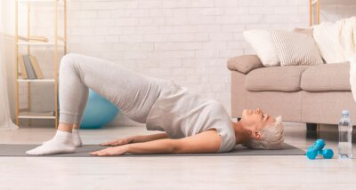 Bild Active senior woman doing back exercise on floor at home
