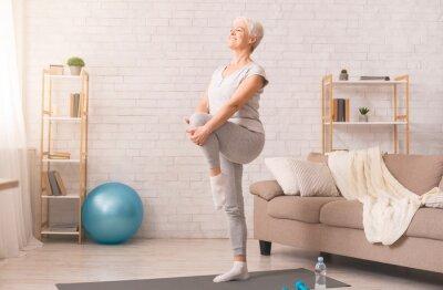 Bild Active senior woman doing legs exercise at home