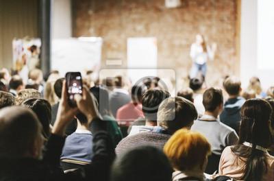 Bild Adult students listen to speaker in auditorium. Rear view.