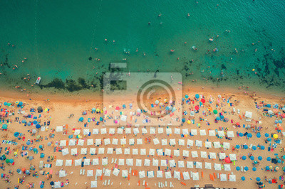 Aerial top view on the beach. People, umbrellas, sand and sea waves.