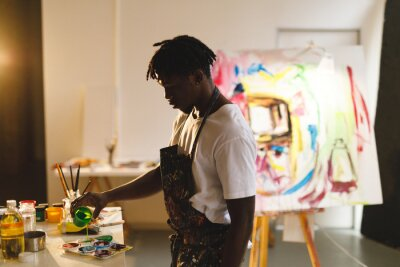 Bild African american male painter at work holding paint in art studio