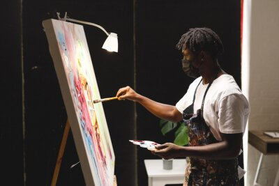 Bild African american male painter wearing face mask painting on canvas in art studio