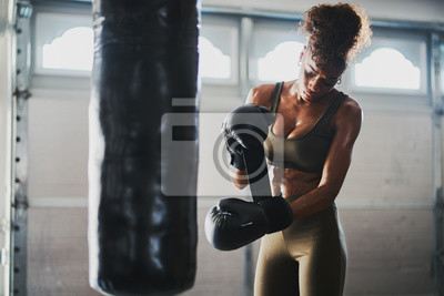 Bild african american woman covered in sweat from boxing punching bag taking off gloves