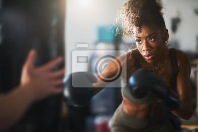 Bild african american woman striking punching bag in home gym