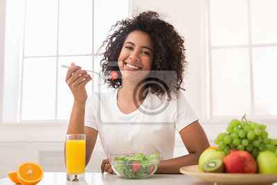 Bild African-american woman with vegetable salad and fresh juice