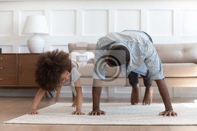 Bild African father and little daughter do push-up exercise indoors