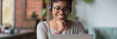 Bild African girl wear headphones looks at pc screen watch movie, online webinar, enjoy virtual study with tutor, teacher interact with trainee via video call, horizontal banner for website header design