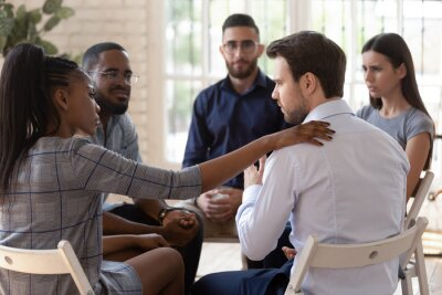 Bild African psychologist supporting caucasian male rehab session participant