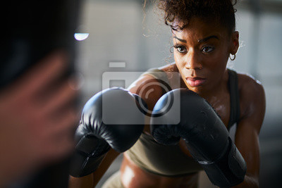 Bild african woman boxing with punching bag in garage gym