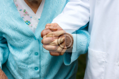 Ältere Dame mit dem Arzt, Hand in Hand
