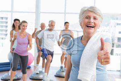 Ältere Frau, die Daumen gestikulieren, sich mit Menschen die Ausübung