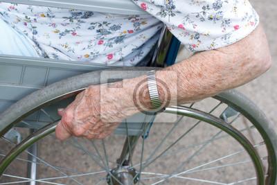 Ältere Hand auf Rad des Rollstuhls