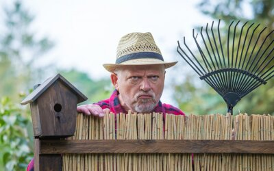 Bild An elderly man with hat looks angry and watching over a garden fence. Concept problems with the neighborhood.