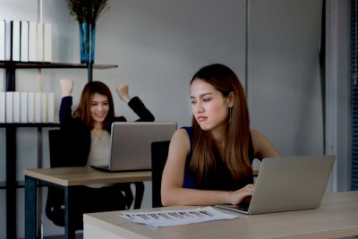 Bild Angry envious Asian business woman looking successful competitor colleague in office. Low key toned image