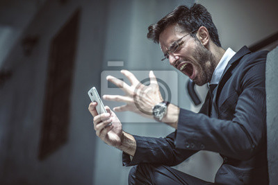 Bild Angry, furious business man shouting at his cell phone, sitting outside a building
