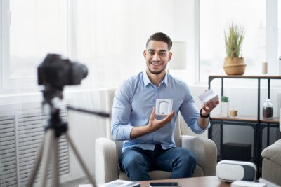 Bild Arab male vlogger making video review of new wireless earphones, using professional camera at home