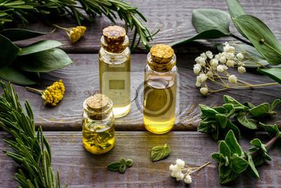 Bild Aromatherapy. Essential oils in small bottles near fresh herbs on dark wooden background