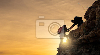 Bild Asia couple hiking help each other silhouette in mountains with sunlight.
