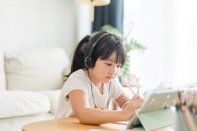 Bild Asian girl student online learning at home.study online video call zoom teacher, kid girl learn english language online with tablet.
