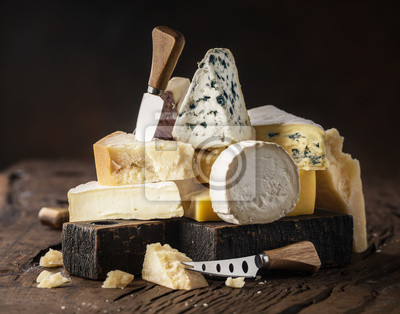 Bild Assortment of different cheese types on wooden background. Cheese background.