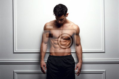 Bild Athlete, muscular man at the white wall poses shirtless, showing six pack abs, white background.