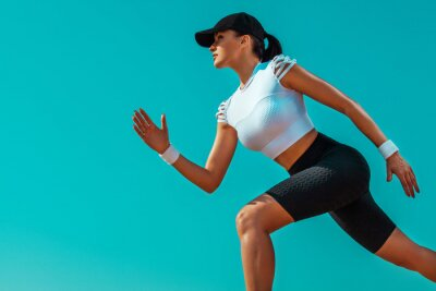 Athlete runner and sprinter. Girl fit athlete running on the sky background. The concept of a healthy lifestyle and sport. Woman in black and white sportswear.