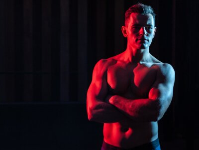 Bild Athletic handsome man athlete with naked torso in red blue gradient neon light on black background