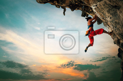 Bild Athletic Woman climbing on overhanging cliff rock with sunset sky background.