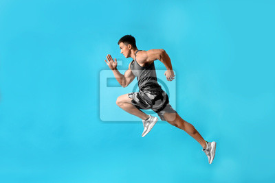 Bild Athletic young man running on light blue background, side view