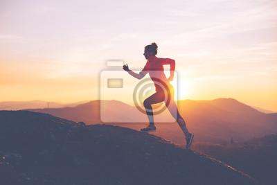 Bild Athletisches Mädchen beendet einen Lauf in den Bergen bei Sonnenuntergang. Sport enge Kleidung. Absichtliche Bewegungsunschärfe.