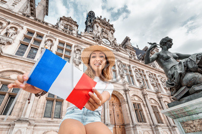 Bild Attractive girl traveler with a french flag enjoys the view of the stunning Gothic architecture of the old town Hall in Paris. Your holidays and adventures in France