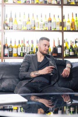 Bild Attraktiver junger Mann sitzt auf einem Sessel mit Glas Wein und Notizbuch
