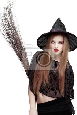 Auffällige junge Frau im Hexenkostüm mit einem Besen