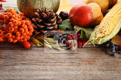 Bild Autumn leafs with berries and vegetables on grey wooden table
