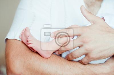 Baby-Füße auf den Händen des Vaters